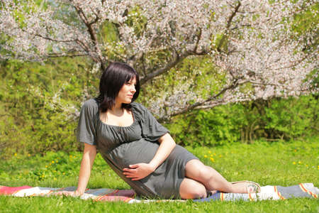 expectant mother on open air under blossom aple tree