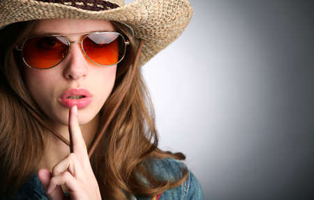 girl in hat and with finger near lips