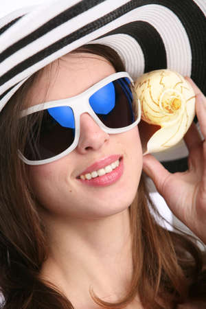 girl in striped hat listens seashell and smiles Stock Photo - 5352448