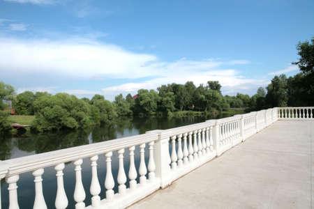 white balustrade ashore calm river under blue sky photo