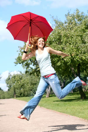 happy woman jumping with a red umbrella in the garden