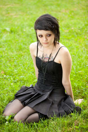 girl in gothic style sits on green grass