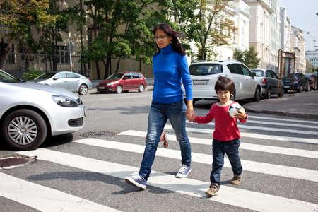 Moeder en zoon zijn op een zebrapad in de stad