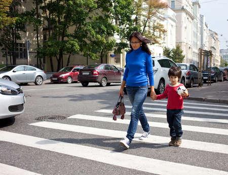 vrouw met een kind aan de hand van een zebrapad in de stad