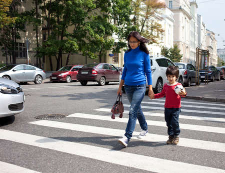 woman with a child going on a pedestrian crossing in the city photo