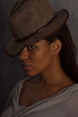 dark portrait of a black girl in gray hat photo