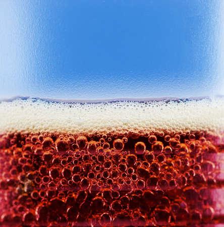 cola avec des bulles et de la mousse de près