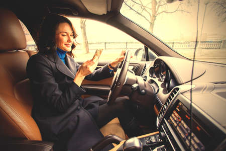 beautiful dark-haired middle-aged woman with a smartphone in hand. driving a car.  image filter retro style