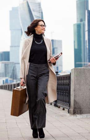 Bella donna di mezza età sorridente in un cappotto luminoso va con una cassa di legno e libri in mano lungo il lungomare sullo sfondo i grattacieli