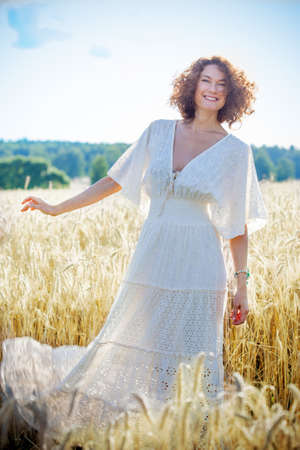 Fashion. Smiling beautiful middle-aged woman dressed in white fashionable dress in the field among the ears wheat. summer season Stock Photo