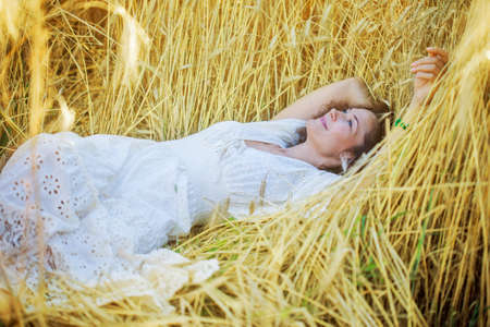 beautiful smiling woman in white dress lying in the field among the ears of wheat. contemplation Stock Photo
