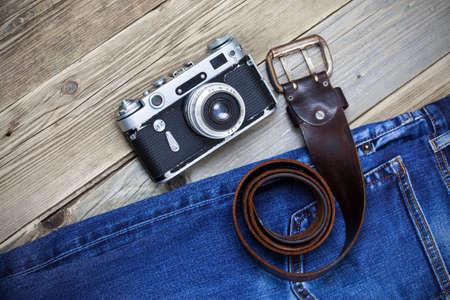 old blue jeans, vintage leather belt and ancient rangefinder camera. still life in a nostalgic manner Stock Photo