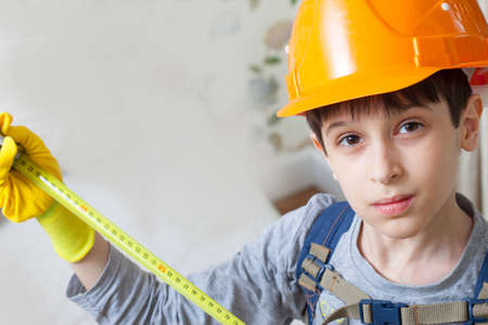 boy in a protective helmet with a measuring tape. The image of the builder Stock Photo