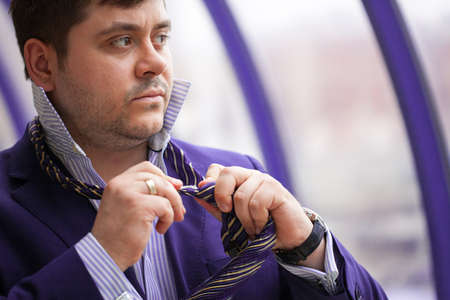 Serious businessman tying his tie before a business meeting