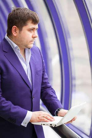 businessman standing near a window with a laptop Stock fotó