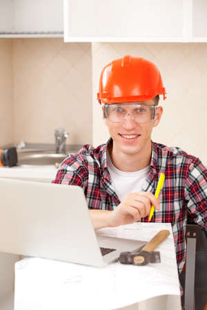 worker in protective helmet with a pen in hand and a computer on a desk on the workplace
