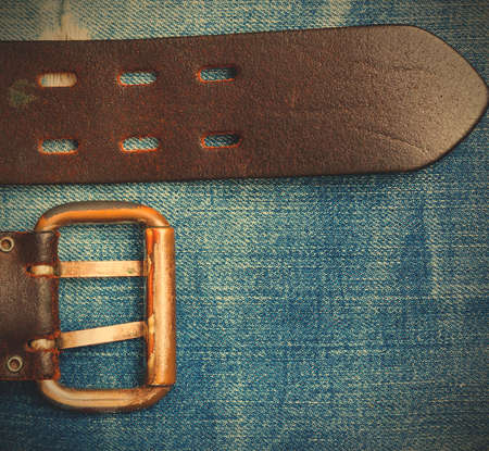 Old leather belt with a buckle on the jeans background with copy space, instagram image style Stock Photo