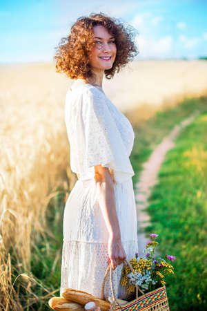 fashion. Smiling beautiful woman in a white dress with a basket with bread and milk on a path in a field under a blue sky