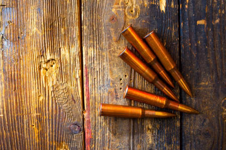 five rifle cartridges on vintage wooden surface