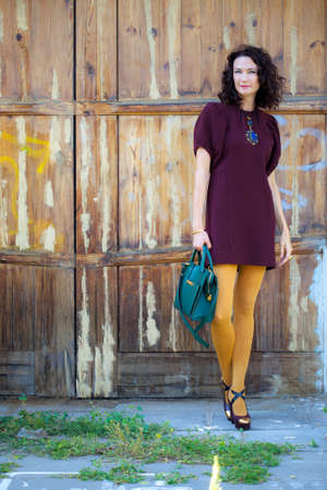 fashion, beauty. beautiful middle-aged brunette in burgundy dress near the vintage wooden gate. vintage style