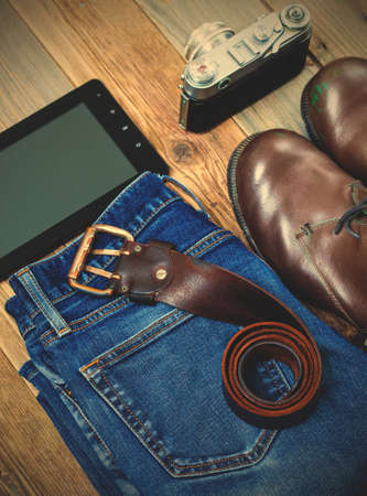 traveler set with a leather belt, digitizer, rangefinder camera, blue jeans and brown boots.