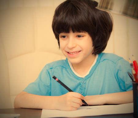 smiling child doing homework with computer, portrait. Standard-Bild