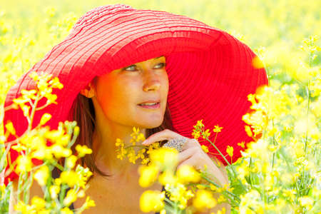 beautiful woman in a red hat on a sunny day amidst wildflowers. portrait, close-up. fashion, style