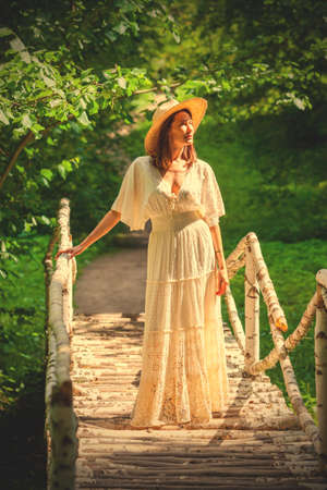 summer fashion and style. beautiful woman in a white dress and hat stands on a birch bridge in a park among trees.