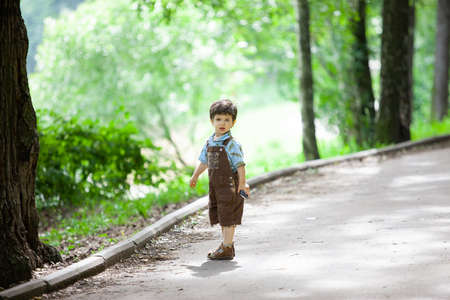 A little boy alone stands on a walkway in an old park. Summer walk