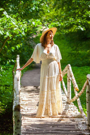 summer fashion and style. beautiful woman in a white dress and hat stands on a birch bridge in a park among trees