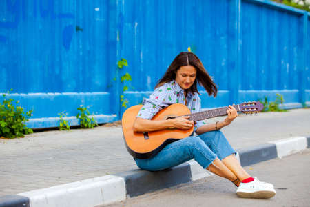 Beautiful smiling woman in jeans sits on a road curb and plays the guitar. Street musician. fashion. Fashion and Style