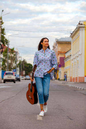 beautiful woman with a guitar walking down the street and smiling. fashion, style, music Stock Photo