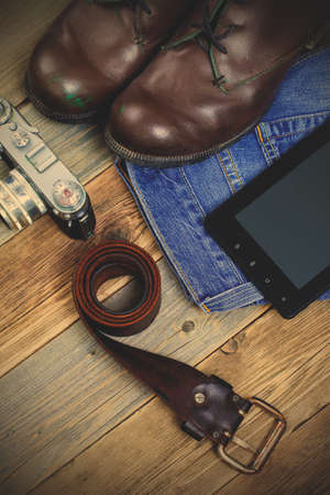 traveler set with a leather belt, digitize, rangefinder camera, blue jeans and brown boots on old boards of table.