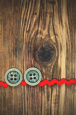 old red tape and two vintage classic buttons on a textured surface aged boards.