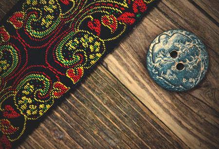 old band with embroidered ornaments and vintage button on a textured surface aged boards.