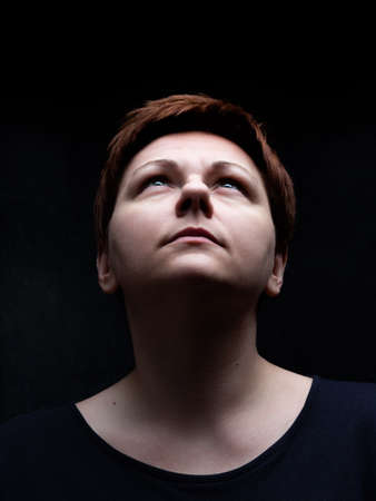 Portrait of short hair woman looking upward against black background. Spiritual expression on enlightened face, eyes focused on the light.