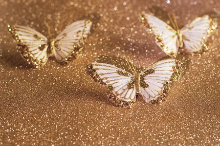 Sparkly gold and white butterflies on a sparkly gold glitter background.