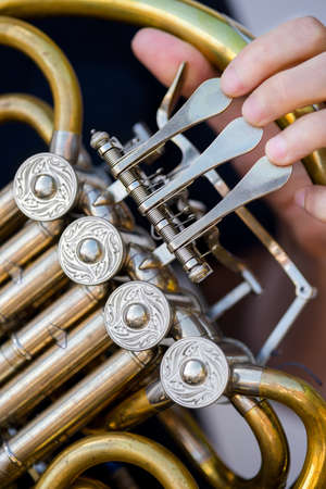 nickle: Caucasian male horn player holding rotors on his old golden french horn Stock Photo