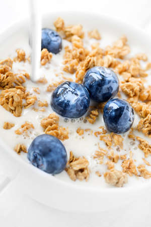 Healthy breakfast with oats granola  and blueberries with milk poured on it on white wooden background