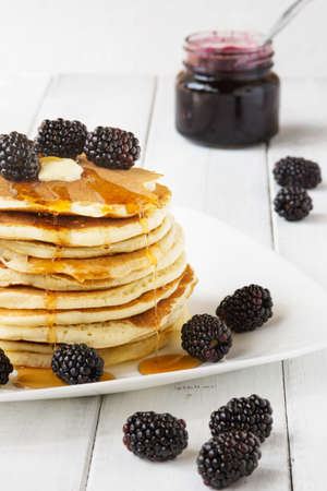 Stack of old-fashioned american pancakes with blackberry and maple syrup photo