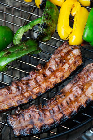 bell peppers: Two thick pieces of bacon on grill with yellow and green bell peppers