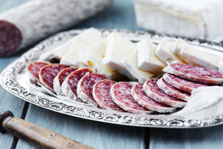 air dried salami: Pieces of brie cheese and air dried salami on a tray Stock Photo