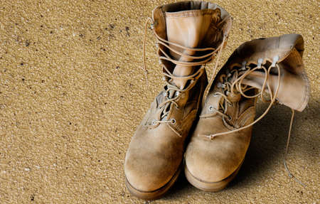 iraq war: US Army uniform boots on sandy background (war concept) Stock Photo