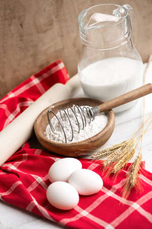 Baking ingredients: eggs,flour,milk on vibrant red towel photo