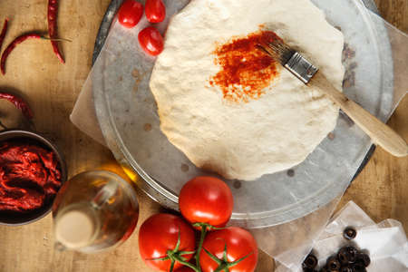 Uncooked pizza dough being brushed with tomato paste on rustic background photo