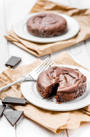 Two chocolate fondants on white rustic wooden table Stock fotó