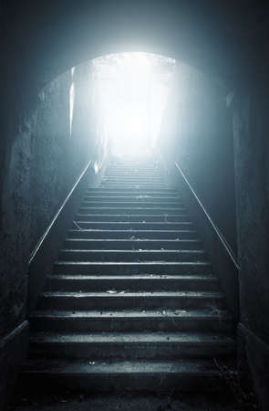 Old abandoned stairs going up to the light. Hope concept