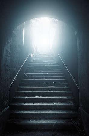 Oude verlaten trap omhoog naar het licht. Hoop begrip