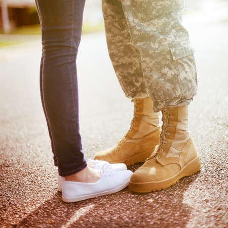 Jong militair paar kussen elkaar, het homecoming concept, warm oranje toning toegepast Stockfoto
