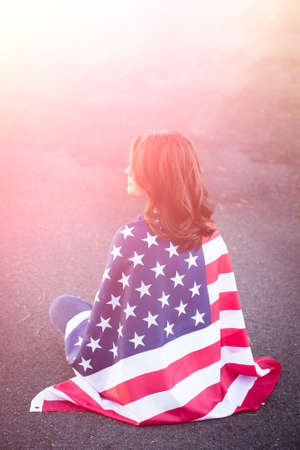 homecoming: Dreaming patriot woman sitting down with american flag wrapped around her. Deployment, military life and relationship concept